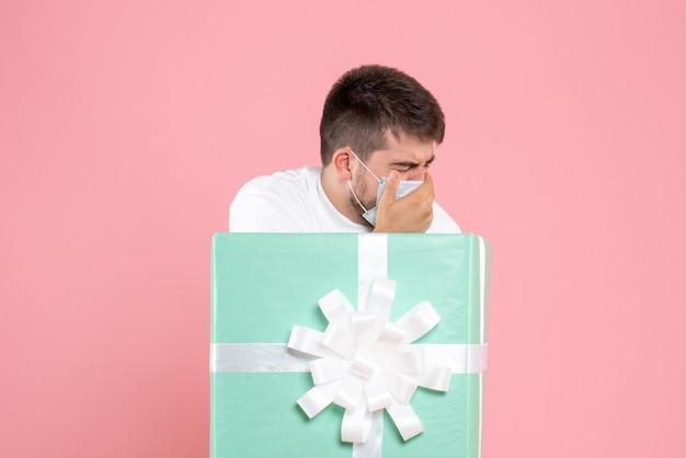 Вид спереди молодого человека внутри настоящей коробки в маске, чувствуя себя больным на розовой стене