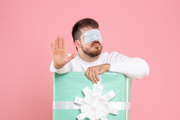 Вид спереди молодого человека внутри настоящей коробки в маске на его глазах на розовой стене
