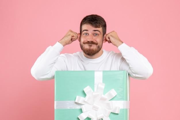 분홍색 벽에 재미있는 얼굴을 만드는 선물 상자 안에 젊은 남자의 전면보기
