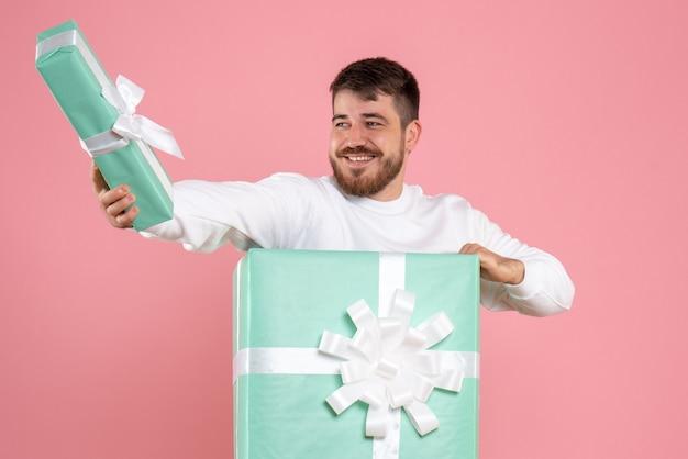 Вид спереди молодого человека внутри подарочной коробки на розовой стене