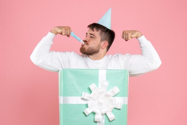 분홍색 벽에 선물 상자 안에 젊은 남자의 전면보기
