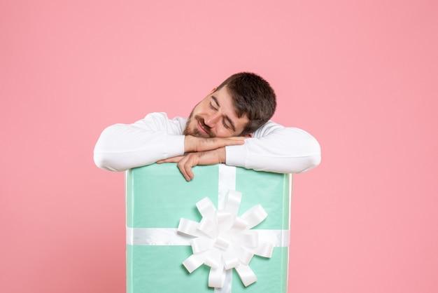 분홍색 벽에 잠자는 선물 상자 안에 젊은 남자의 전면보기