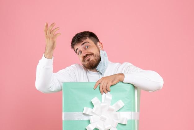 淡いピンクの壁に彼のマスクを脱いでプレゼントボックス内の若い男の正面図
