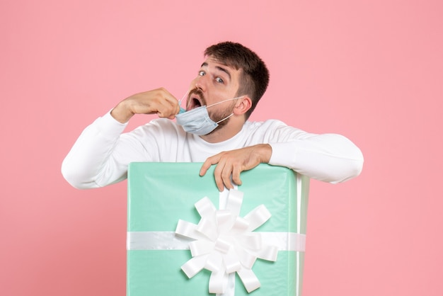 ピンクの壁に彼のマスクを脱いでプレゼントボックス内の若い男の正面図
