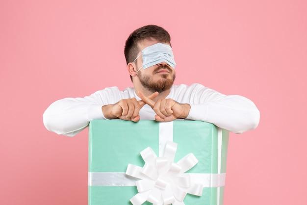 Вид спереди молодого человека в настоящей коробке в маске на глазах на розовой стене