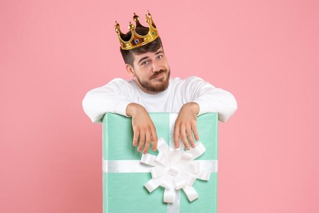 ピンクの壁に王冠とプレゼントボックス内の若い男の正面図