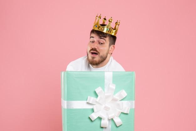 분홍색 벽에 왕관과 함께 선물 상자 안에 젊은 남자의 전면보기
