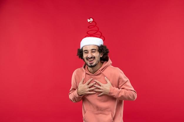 赤い壁で笑っている若い男の正面図