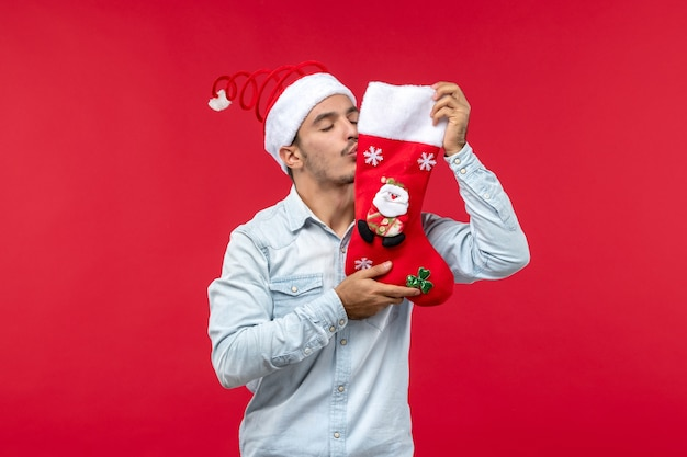 Вид спереди молодого человека, целующего рождественский носок на красной стене