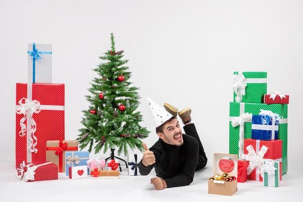Вид спереди молодого человека, лежащего вокруг праздничных подарков на белой стене