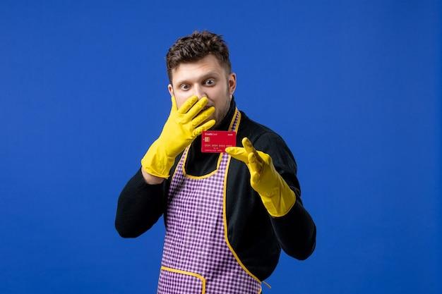 Вид спереди молодого человека, смотрящего на свою карточку на синей стене