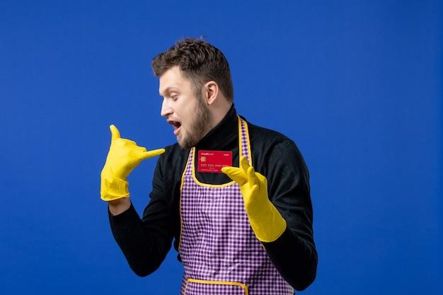 파란색 벽에 카드를 들고 전화 제스처를 만드는 젊은 남자의 전면 보기