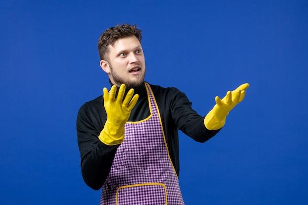 파란색 벽에 서 있는 손을 여는 젊은 남자의 전면 보기