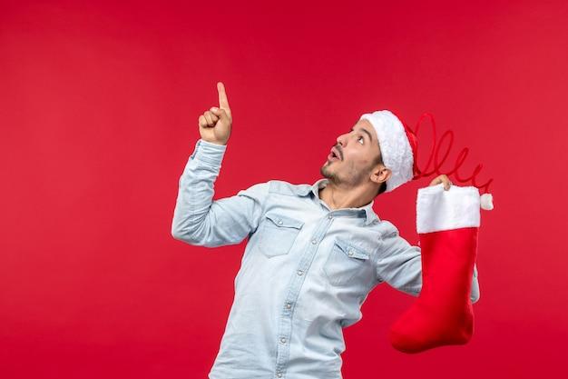 Вид спереди молодого человека, позирующего с рождественским носком на красной стене