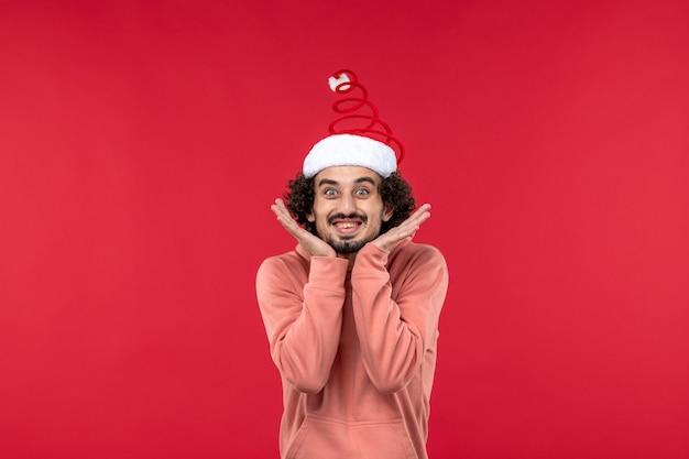 붉은 벽에 흥분된 표정으로 포즈를 취하는 젊은 남자의 전면보기
