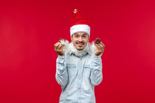 Вид спереди молодого человека, готовящегося к новому году на красной стене