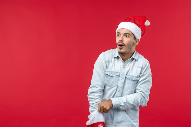 赤い壁の靴下の中に手を入れている若い男の正面図