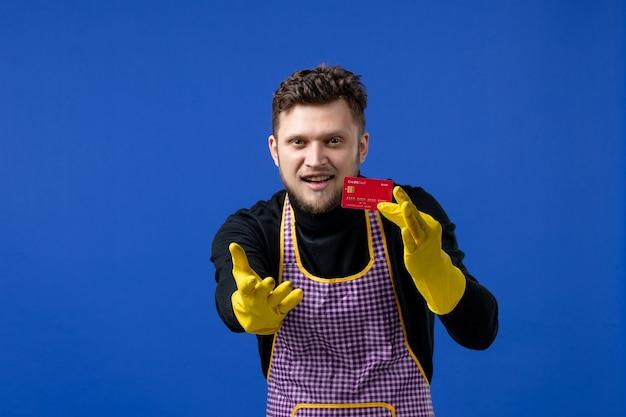 파란색 벽에 카드를 들고 손을 내밀고 있는 젊은 남자의 전면 모습