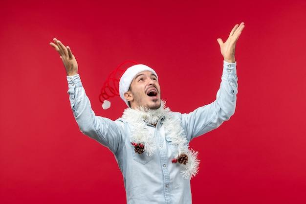 赤い壁に新年のために喜んでいる若い男の正面図