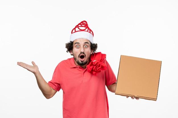 흰 벽에 배달 음식 상자에 충격을 받은 젊은 남자의 전면 보기