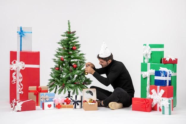 Вид спереди молодого человека, сидящего вокруг праздника, украшает маленькое деревце на белой стене
