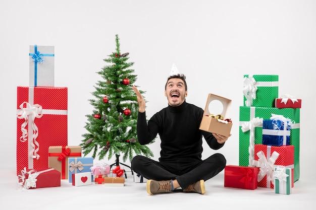 休日の周りに座っている若い男の正面図は白い壁に木のおもちゃを持ってプレゼント