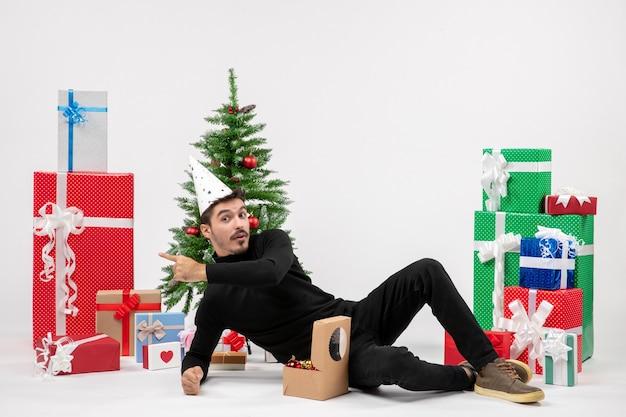 白い壁に休日のプレゼントの周りに座っている若い男の正面図
