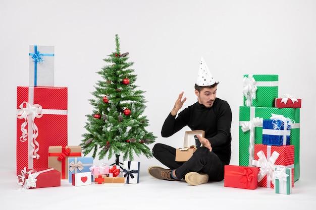 Вид спереди молодого человека, сидящего вокруг праздничных подарков на белой стене