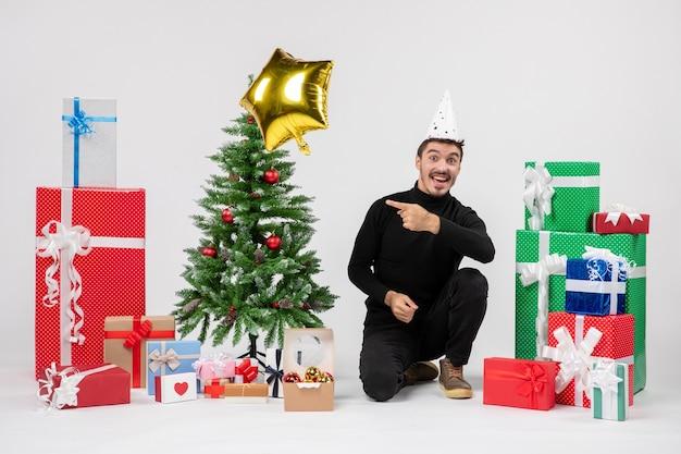 흰 벽에 선물과 골드 스타 풍선 주위에 앉아있는 젊은 남자의 전면보기