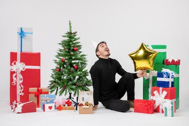 선물 주위에 앉아 흰 벽에 골드 스타 그림을 들고 젊은 남자의 전면보기