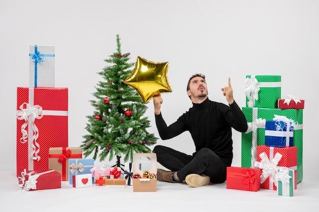 Вид спереди молодого человека, сидящего вокруг подарков и держащего золотую звезду на белой стене