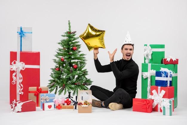 プレゼントの周りに座って、白い壁に金の星の図を保持している若い男の正面図
