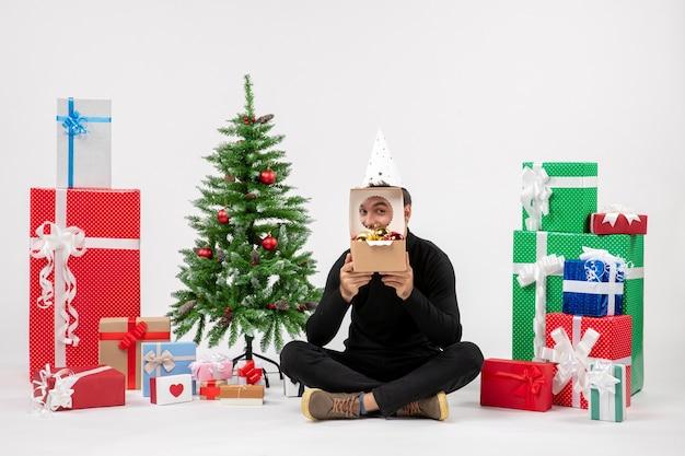 白い壁にプレゼントの周りに座っている若い男の正面図