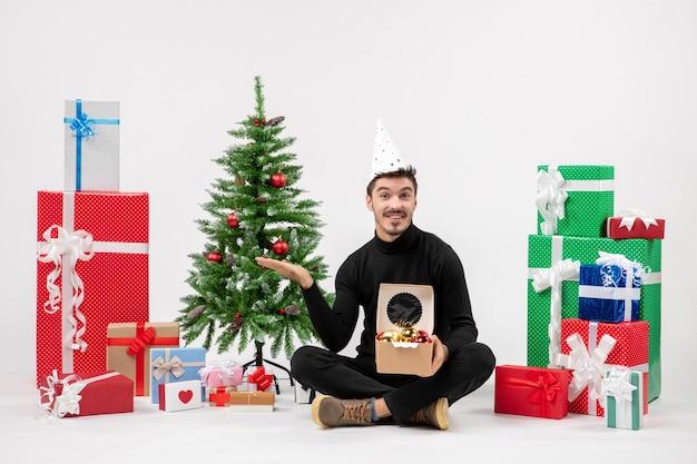 Вид спереди молодого человека, сидящего вокруг подарков на белой стене