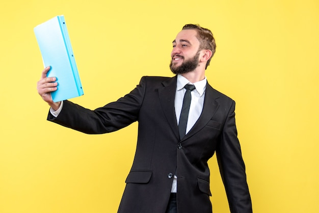 黄色の青いフォルダーを噛んでいる間、ビジネスマンの笑顔の若い男の正面図は満足しているように見えます