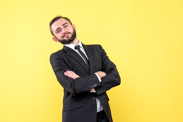 黄色の手を交差させる十字架とビジネスマンの笑顔の若い男の正面図