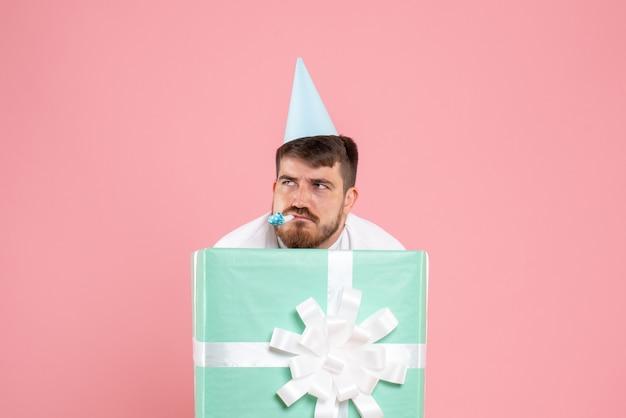 ピンクの壁に退屈を感じてプレゼントボックスの中に立っている若い男の正面図