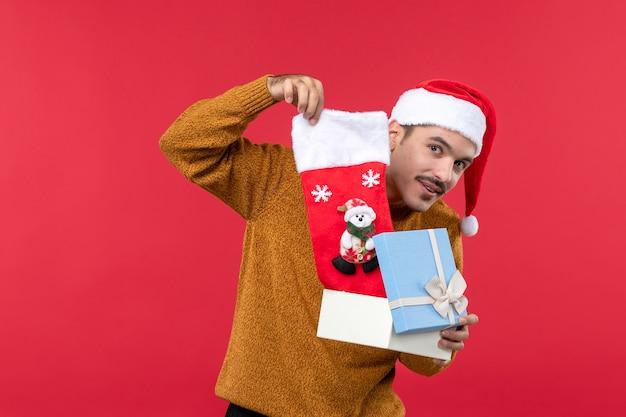Вид спереди молодого человека, принимающего рождественский носок из коробки на красной стене