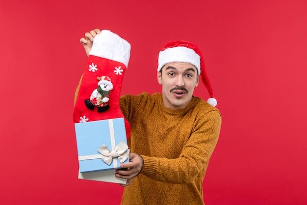 Вид спереди молодого человека, вынимающего рождественский носок на красной стене