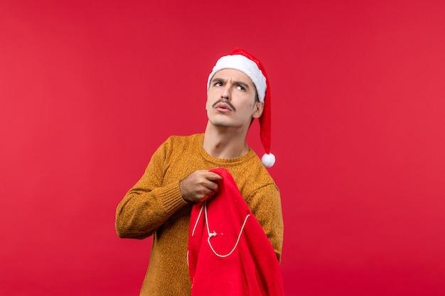 赤い壁の上のバッグから贈り物を取り出している若い男の正面図