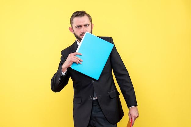 若い男の思いやりのあるビジネスマンの正面図は黄色の青いフォルダーで彼の下の顔に触れます