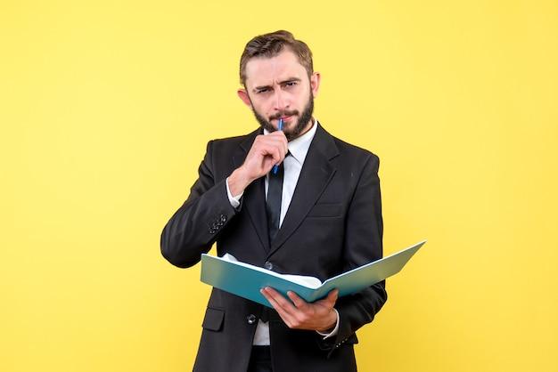 彼の口にペンを触れているビジネスマン思慮深く若い男の正面図は黄色の青いフォルダーを保持します