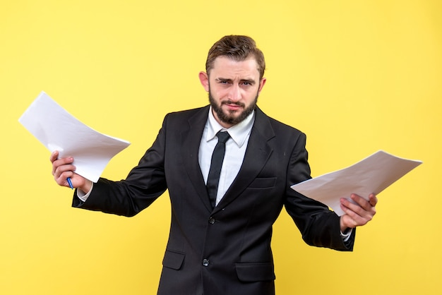 黄色の両手に白紙を保持している青年不確かなビジネスマンの正面図