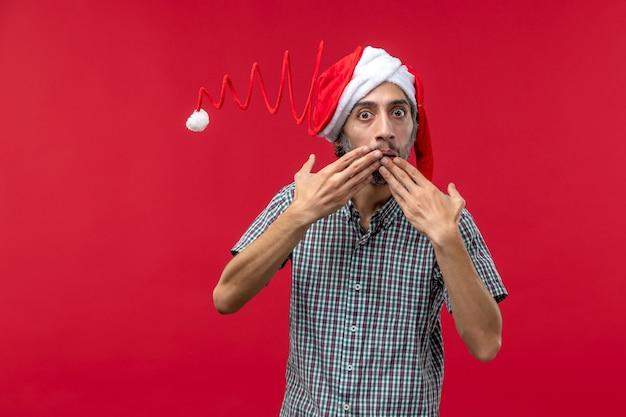 Вид спереди молодого человека в кепке рождественской игрушки на красной стене