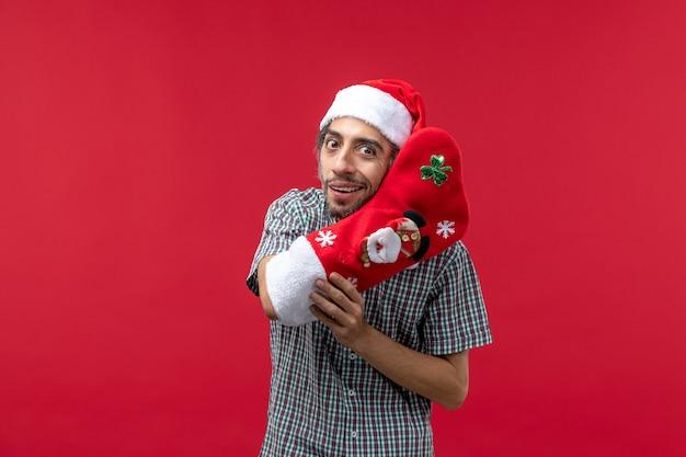 Вид спереди молодого человека в красном рождественском носке на красной стене