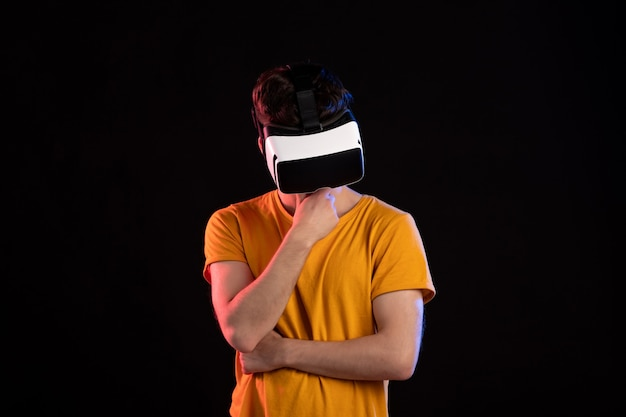 暗いゲームビデオでバーチャルリアリティヘッドセットを身に着けている若い男の正面図d