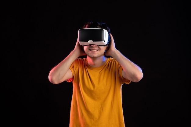 Вид спереди молодого человека в гарнитуре виртуальной реальности на темной стене
