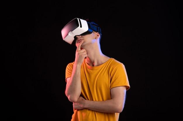 어두운 벽에 가상 현실 헤드셋을 착용하는 젊은 남자의 전면보기
