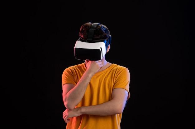 어두운 벽에 vr 헤드셋을 착용하는 젊은 남자의 전면보기