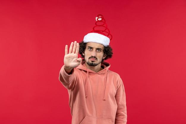 붉은 벽에 화난 표정으로 젊은 남자의 전면보기